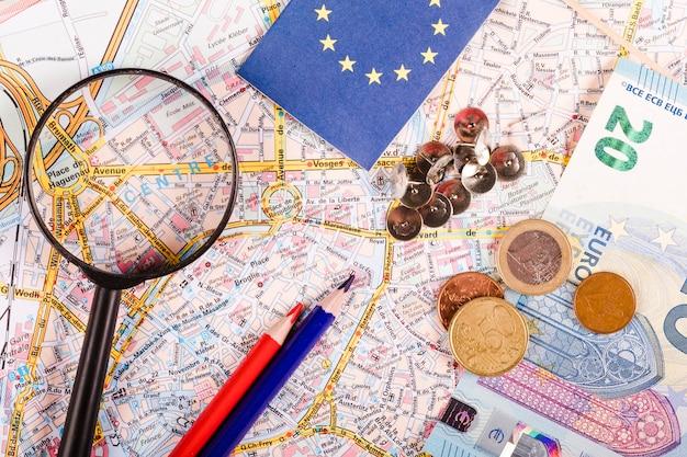 Euro monete con lente di ingrandimento, puntine da disegno, matite e bandiera sulla mappa del mondo