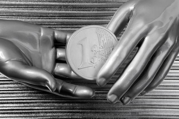 Euro monete d'argento in mani di robot futuristico
