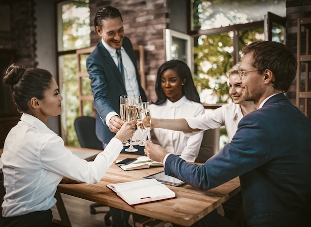Evento di affari, gente sorridente dell'ufficio che tiene i vetri con alcool