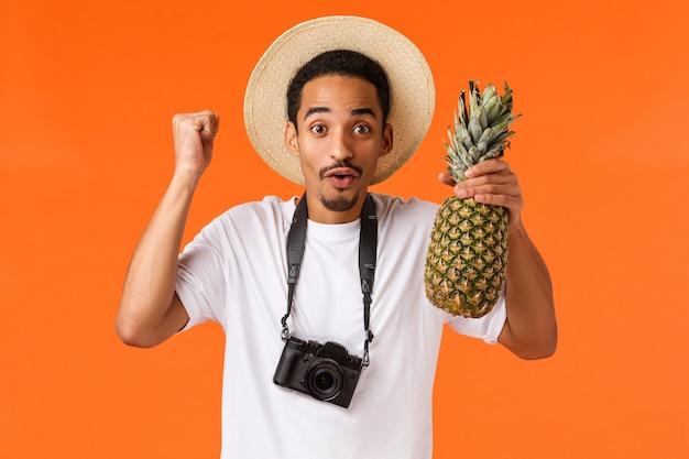 Evviva vacanza e frutti tropicali. l'uomo afroamericano allegro allegro finalmente viaggia all'estero, divertendosi durante il viaggio, pompa del pugno e tenendo l'ananas, stando con sopra la parete arancio