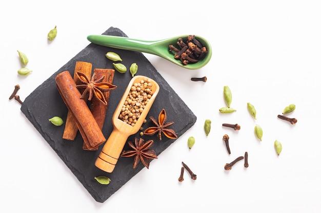 Exotic herbal food concept mix delle spezie organiche su una lastra di pietra ardesia nera con copia