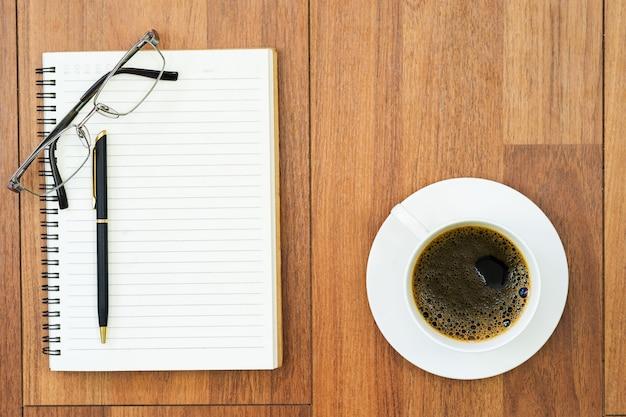 Eyeglasse e blocco note con la tazza di caffè sulla piattaforma di legno