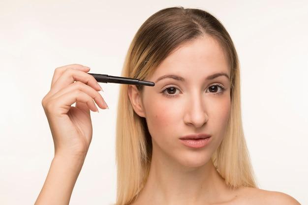 Eyeliner di bella ragazza bionda holding
