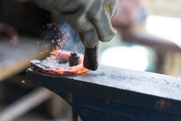 Fabbri che lavorano nella fucina e facendo un ferro di cavallo.