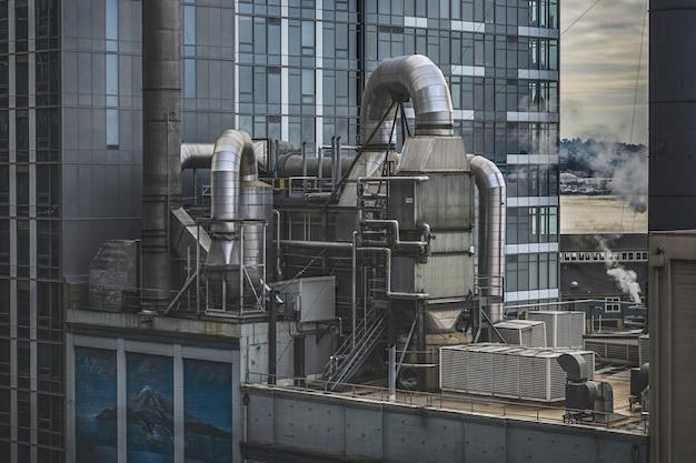 Fabbrica circondata da grattacieli con vegetazione