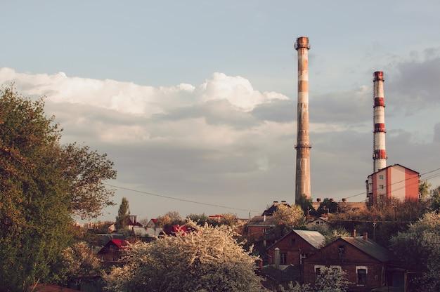 Fabbrica del tubo di fumo contro il cielo blu e vicino alla casa.