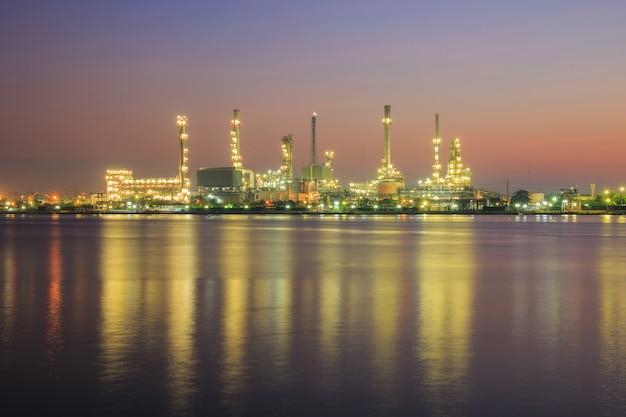 Fabbrica della raffineria di petrolio in cielo di alba e della siluetta