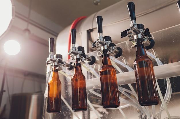 Fabbrica di birra che versa birra in bottiglie di vetro su linee di trasporto. lavoro industriale, produzione automatizzata di cibi e bevande. lavoro tecnologico in fabbrica.