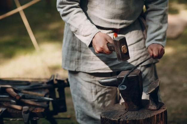 Fabbro con martello al lavoro e strumento
