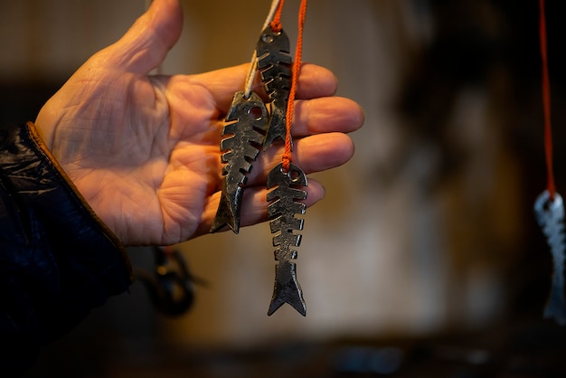 Fabbro elementi decorativi in metallo pesce appeso alla fucina, officina. fatto a mano, artigianato e concetto di fabbro