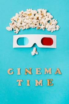 Faccia antropomorfa fatta con popcorn e occhiali 3d sopra il testo del tempo del cinema su sfondo blu