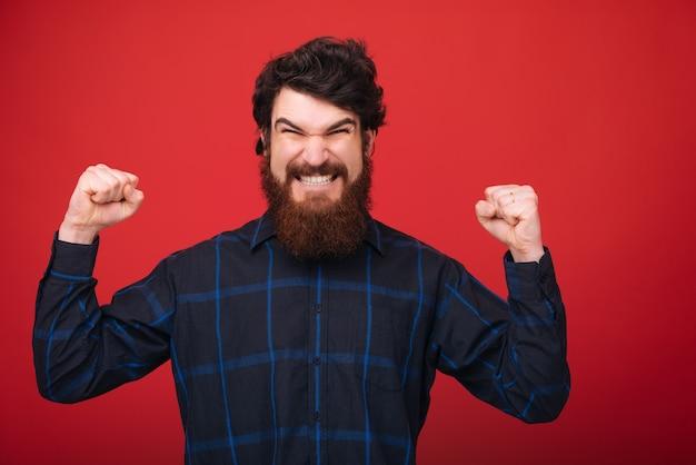 Faccia arrabbiata, eccitato ragazzo con la barba che fa un gesto celebrativo, con resing mani su backgroud rosso