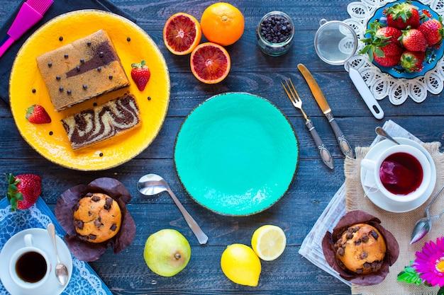 Faccia colazione con caffè e tè con differenti pasticcerie e frutti su una tavola di legno