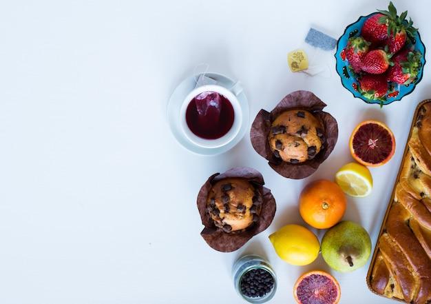 Faccia colazione con caffè e tè con differenti pasticcini e frutti su una tavola di legno bianca