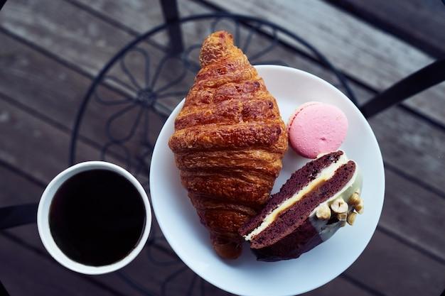 Faccia colazione con il croissant e dessert, caffè o tè in tazza di plastica, nel villaggio, all'aperto, natura.