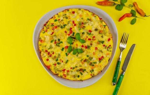 Faccia colazione con la frittata di verdure su superficie gialla