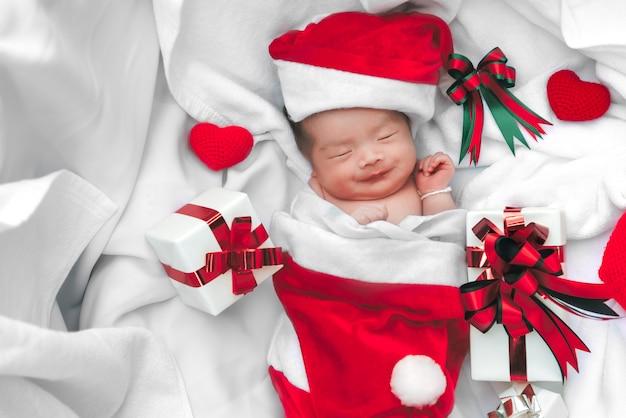 Faccia da bambino appena nato in cappello di natale con confezione regalo da babbo natale e cuore di filato