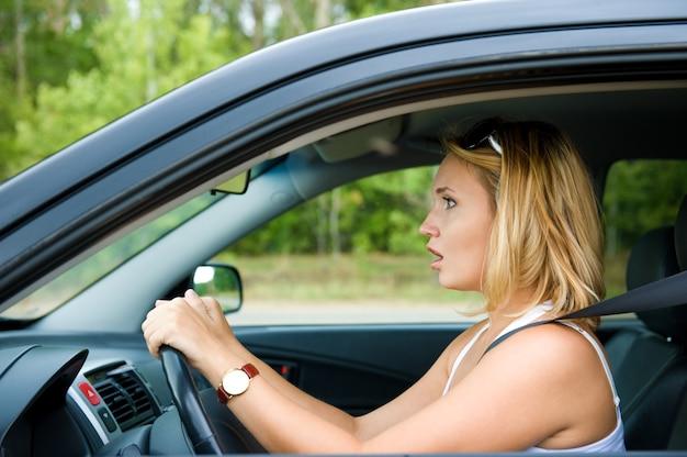 Faccia di profilo della donna spaventata che si siede in macchina e tiene la ruota - all'aperto