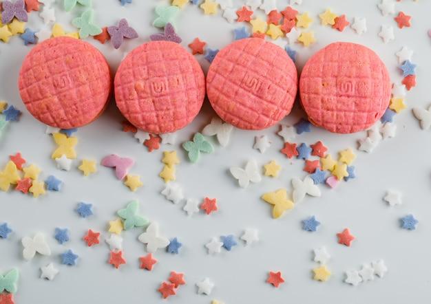 Faccia festa i biscotti con lo zucchero spruzza sulla tavola bianca,