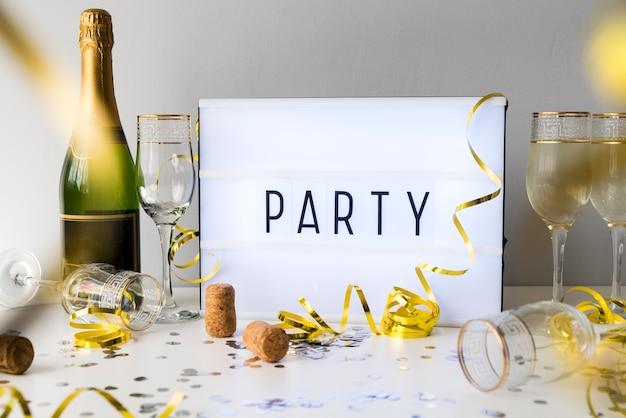 Faccia festa il testo sulla scatola leggera con la bottiglia del champagne e gli oggetti decorativi