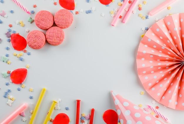 Faccia festa le decorazioni con lo zucchero spruzza, biscotti sulla tavola bianca