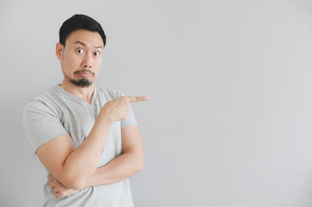 Faccia scossa dell'uomo in maglietta grigia con punto della mano su spazio vuoto.