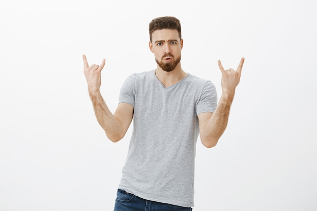 Facciamo rock questa festa. ritratto di modello maschio bello ed elegante entusiasta con barba e baffi che mostra gesto di rock-n-roll imbronciato e accigliato godendo di concerti e musica contro il muro bianco