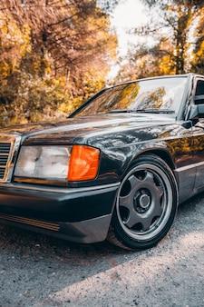 Facciata anteriore e luci di un'auto berlina nera d'annata.