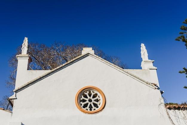 Facciata bianca di una vecchia casa colonica mediterranea, al sole.