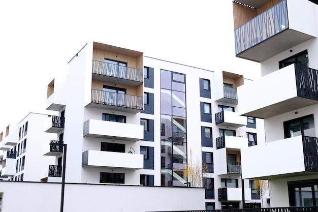 Facciata di un moderno condominio con balcone e pareti bianche. nessuno.