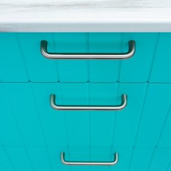 Facciata in legno blu di mobili da cucina a strisce sottili con maniglie cromate.