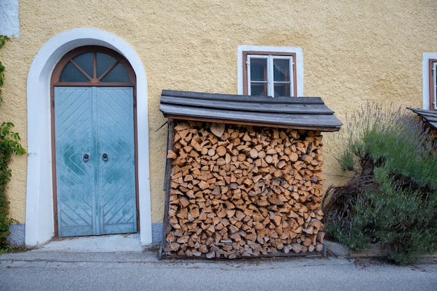 Facciata sulla cornice della finestra di una vecchia casa di legno di una casa con un firewood
