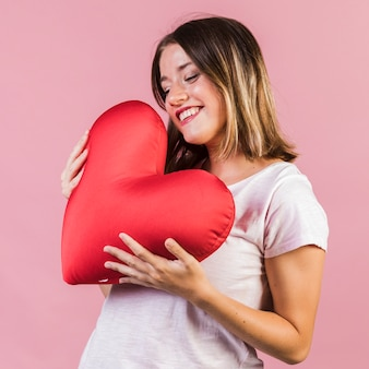 Faccina che tiene un cuscino a forma di cuore