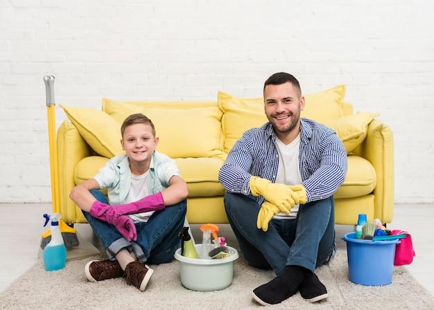 Faccina padre e figlio in posa accanto a prodotti per la pulizia