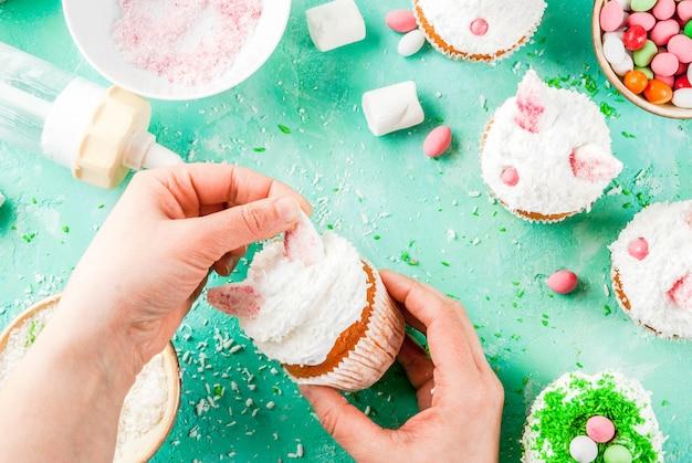 Facendo cupcakes di pasqua, la persona decora torte con orecchie da coniglio e uova di caramella, cornice, mani della ragazza in foto
