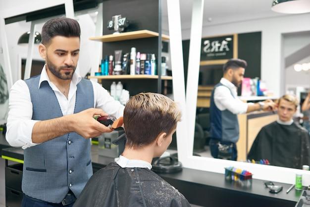 Facendo nuova acconciatura moderna per giovane nel negozio di barbiere.
