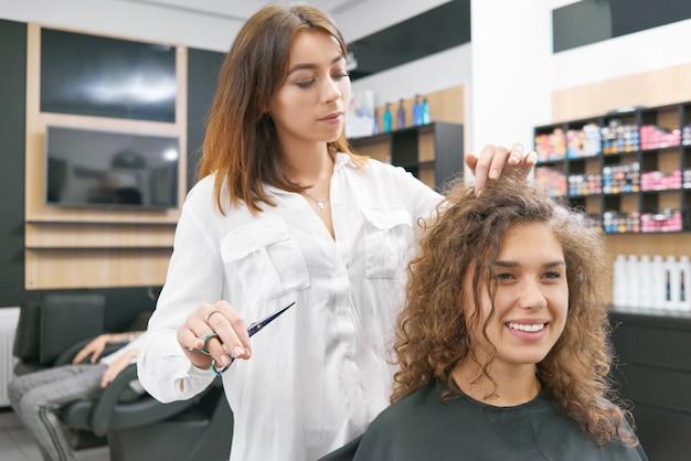 Facendo nuovi hairdress per sorridente cliente femminile ricci.