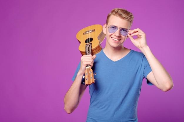 Fachion bellezza uomo divertente con ukulele nelle mani su sfondo viola copyspace