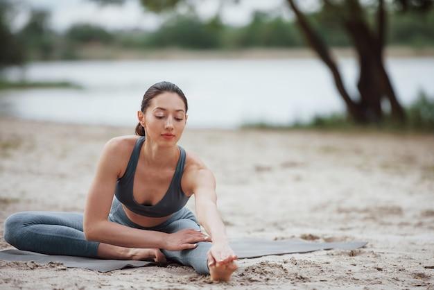 Facile riscaldamento. bruna con una bella forma del corpo in abiti sportivi hanno una giornata di fitness su una spiaggia