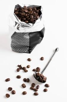 Fagioli arrostiti caffè in sacchetto di plastica e cucchiaio