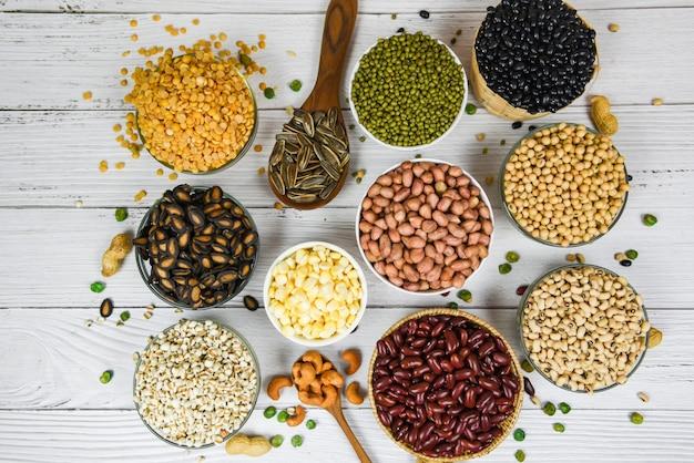 Fagioli di cereali integrali diversi sulla ciotola e legumi semi lenticchie e noci vista dall'alto spuntino colorato - collage vari fagioli mescolano piselli agricoltura di cibo sano naturale per cucinare ingredienti