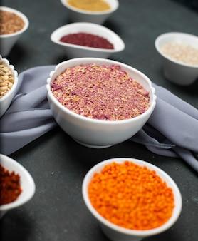Fagioli di lenticchia rossa ed erbe di sumakh in una ciotola bianca sul tavolo