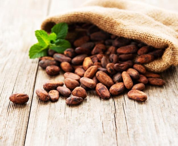 Fagioli grezzi del cacao nella borsa di tela da imballaggio su una tavola di legno