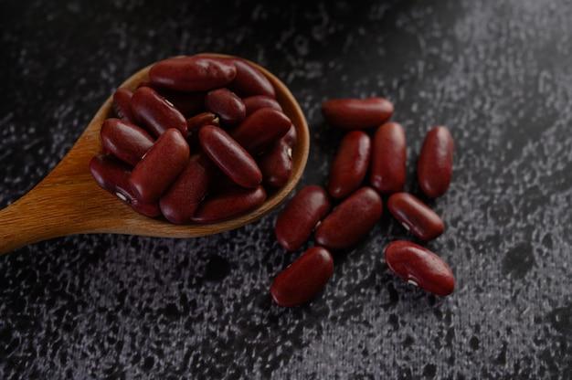 Fagioli rossi in un cucchiaio di legno sul pavimento di cemento nero.