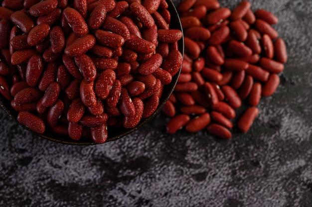 Fagioli rossi in una ciotola di legno e con acqua sprayon il pavimento di cemento nero.