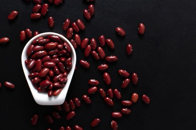 Fagioli rossi in una tazza bianca sul nero. ritmo di copie. vista dall'alto.