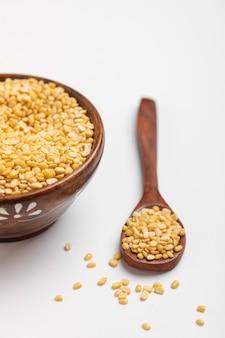 Fagiolo giallo della lenticchia del moung mung dal lenticchia in ciotola del cucchiaio e di legno su fondo bianco