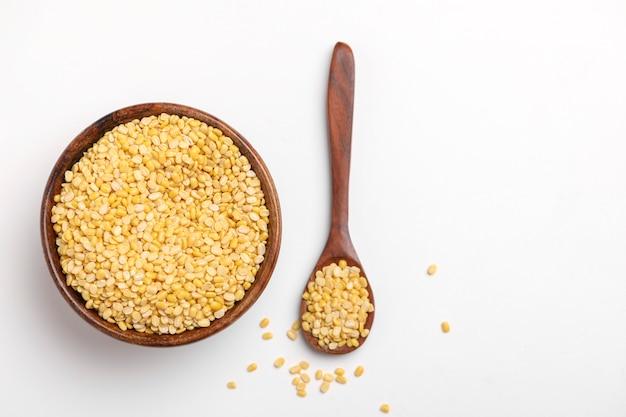 Fagiolo giallo della lenticchia di mung dal mung dal in cucchiaio di legno su fondo bianco