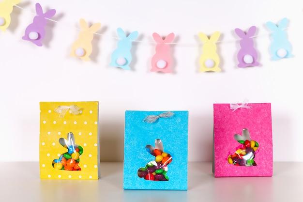Fai da te i dolci del pacchetto di avvolgimento di pasqua in una borsa con una sagoma di coniglio tagliato su uno sfondo bianco.