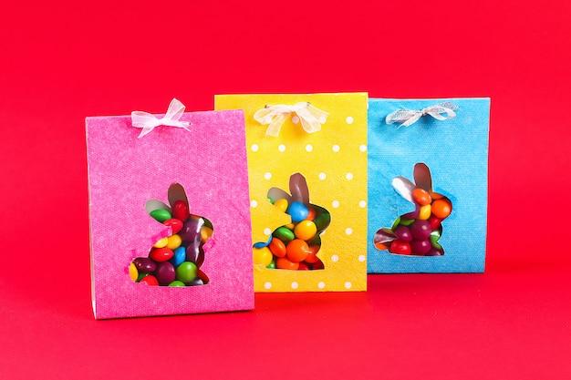 Fai da te i dolci del pacchetto di avvolgimento di pasqua in una borsa con una sagoma di coniglio tagliato su uno sfondo rosso.